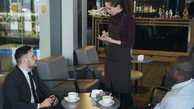 2 мульти-этнических бизнесмена в официально одеждах сидя, усмехаясь и делая заказ в стильном кафе во время перерыв на ланч акции видеоматериалы