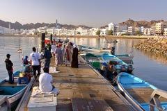 МУСКАТ, ОМАН - 11-ОЕ ФЕВРАЛЯ 2012: Рыболов на рыбах Muttrah стыкует рано утром с карнизом Muttrah на заднем плане Стоковые Изображения