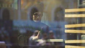 Мусульманская дама в традиционной одежде беседуя на плате сидя в кафе, современной жизни видеоматериал