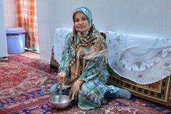 Мусульманская девушка в hijab варит еды дома Стоковые Фото