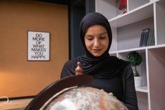 Мусульманская девушка изучая в библиотеке стоковые фотографии rf