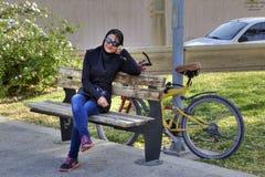 Мусульманская девушка моды сидя самостоятельно на скамейке в парке, Ширазе, Иране Стоковая Фотография