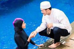 Мусульманская женщина в бассейне приветствуя ее супруга стоковое изображение rf