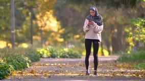 Мусульманская женщина в hijab идет jogging в осеннем парке, стопах для того чтобы посмотреть в смартфон и продолжает побежать акции видеоматериалы
