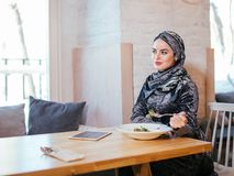 Мусульманская женщина есть на кафе с едой Стоковые Изображения