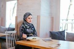 Мусульманская женщина есть на кафе с едой Стоковое фото RF
