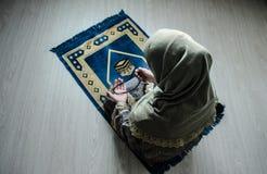 Мусульманская женщина моля для бога Аллаха мусульманского на комнате около окна Руки мусульманской женщины на ковре моля в традиц Стоковое фото RF