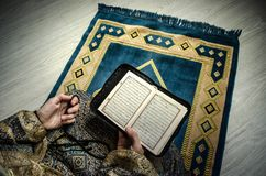 Мусульманская женщина моля для бога Аллаха мусульманского на комнате около окна Руки мусульманской женщины на ковре моля в традиц Стоковые Изображения RF
