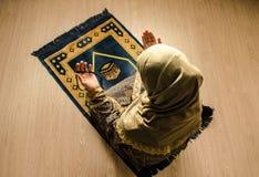 Мусульманская женщина моля для бога Аллаха мусульманского на комнате около окна Руки мусульманской женщины на ковре моля в традиц стоковые фото