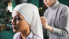 Мусульманская женщина на заднем плане делает исламский тюрбан для красивой невесты Стоковое Фото