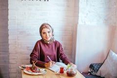 Мусульманская женщина работая в кафе стоковые изображения