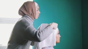 Мусульманская женщина связывая исламский тюрбан для привлекательной невесты Стоковое Фото