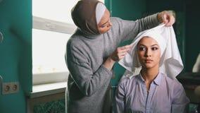 Мусульманская женщина создавая исламскую традиционную одежду свадьбы для красивой невесты Стоковая Фотография RF