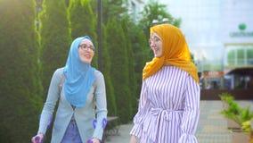 Мусульманская женщина со сломанной ногой на костылях связывает с другой мусульманской женщиной в традиционном шарфе в парке видеоматериал