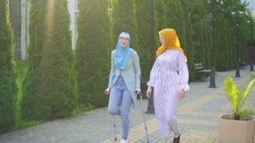 Мусульманская женщина со сломанной ногой на костылях связывает с другой мусульманской женщиной в традиционном шарфе в парке сток-видео