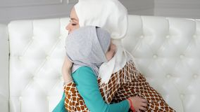 Мусульманская мама и ее маленькая дочь в hijabs обнимают сидеть на софе сток-видео
