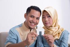 Мусульманские азиатские пары держа домашний знак Стоковые Фото