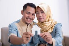 Мусульманские азиатские пары держа домашний знак Стоковые Фотографии RF