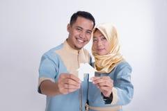 Мусульманские азиатские пары держа домашний знак Стоковая Фотография