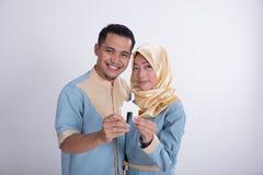 Мусульманские азиатские пары держа домашний знак Стоковое фото RF