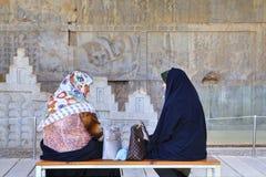 Мусульманские женщины говоря пока сидящ на стенде в музее Persepolis Стоковое Фото
