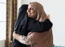 Мусульманские женщины обнимая один другого Стоковые Изображения