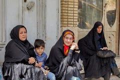 Мусульманские женщины при ребенок сидя на автобусной остановке, Kashan, Иране Стоковые Изображения RF