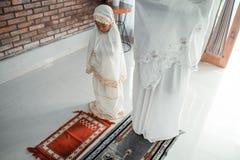 Мусульманский азиатский молить матери и дочери стоковые изображения