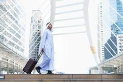 Мусульманский тюрбан и платье носки человека белые идя с местом багажа публично и современной предпосылкой здания Стоковые Фото