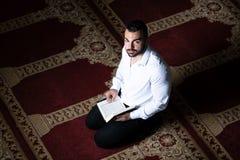 Мусульманский человек слушает на шлемофоне Koran стоковые изображения rf