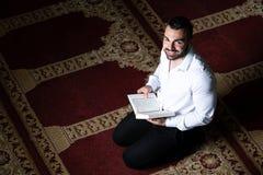 Мусульманский человек слушает на шлемофоне Koran стоковая фотография