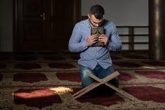 Мусульманский человек целует Koran стоковые фото