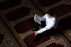 Мусульманский человек читает Koran стоковые фото