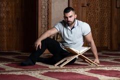 Мусульманский человек читает Koran стоковые изображения