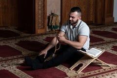 Мусульманский человек читает Koran стоковые фотографии rf
