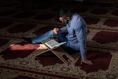 Мусульманский человек читает Koran стоковые изображения rf