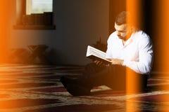Мусульманский человек читает Koran стоковое изображение rf