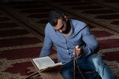 Мусульманский человек читая святую исламскую книгу Koran стоковые фотографии rf