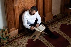 Мусульманский человек читая святую исламскую книгу Koran стоковые изображения