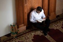 Мусульманский человек читая святую исламскую книгу Koran стоковая фотография