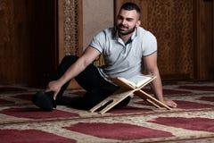 Мусульманский человек читая святую исламскую книгу Koran стоковое изображение