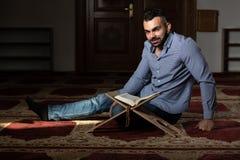 Мусульманский человек читая святую исламскую книгу Koran стоковые фото