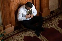 Мусульманский человек читая святую исламскую книгу Koran стоковое фото rf