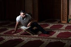 Мусульманский человек читая святую исламскую книгу Koran стоковые изображения rf