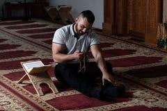 Мусульманский человек читая святую исламскую книгу Koran стоковая фотография rf
