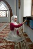 Мусульманская девушка в мечети читая Koran Стоковая Фотография RF