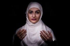 Мусульманская девушка молит изолированный в темноте Стоковые Изображения RF