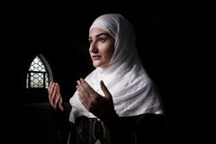 Мусульманская девушка молит изолированный в темноте Стоковое Изображение