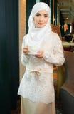 Мусульманская женщина в белом платье свадьбы с чашкой чаю в его руках Стоковые Фотографии RF