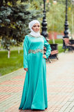 Мусульманская женщина в восточном платье и белой бандане на ее голове в парке Стоковая Фотография